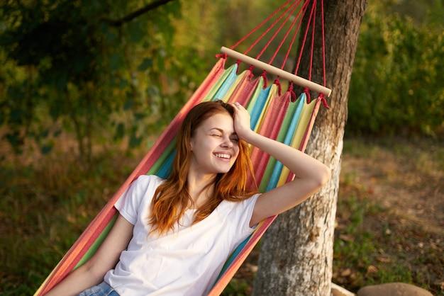 幸せな女性は笑顔モデルを笑って森の屋外のハンモックに横たわっています
