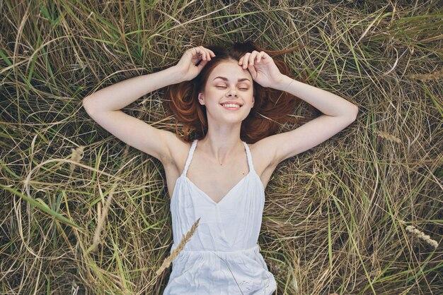 Счастливая женщина лежит на сухой траве и жесты руками белое платье