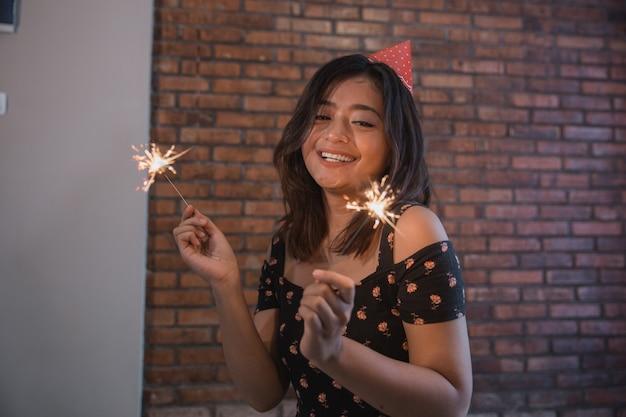 Happy woman lighting sparklers celebrating