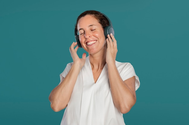 Happy woman listening to music from headphones