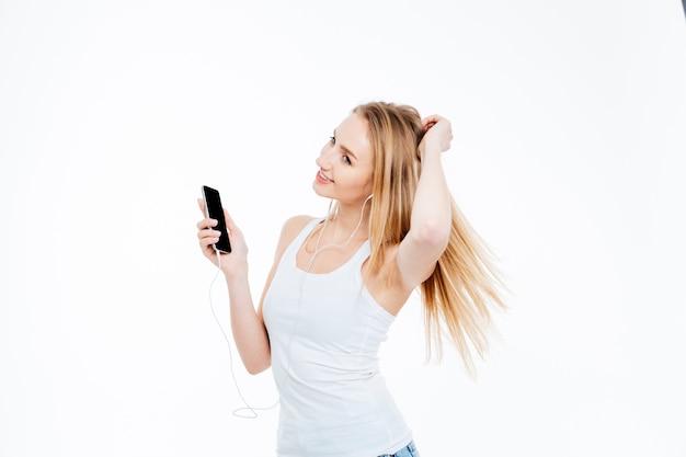 스마트 폰에 행복 한 여자 듣기 음악 흰색 배경에 고립