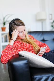 Happy woman listening to music wearing headphones using a smartphone sitting on a sofa