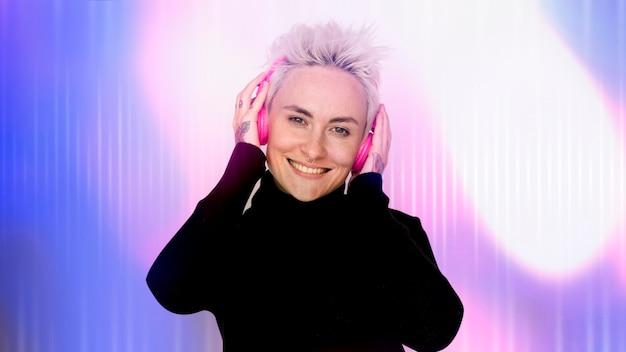 彼女のピンクのヘッドフォンで音楽を聴いて幸せな女性