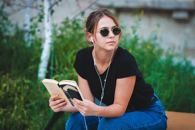 Счастливая женщина слушает музыку в наушниках и читает книгу на улице