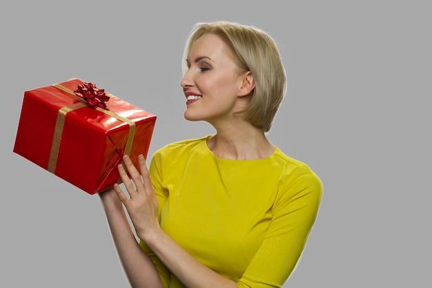 그녀의 손에있는 선물 상자를보고 행복 한 여자. 회색 바탕에 선물 상자를 들고 꽤 웃는 소녀. 특별 이벤트 선물.