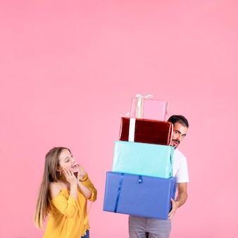 Happy woman looking at man holding stack of gift boxes against pink backdrop