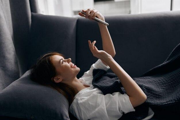 屋内のソファに横たわっているときに電話の画面を見ている幸せな女性