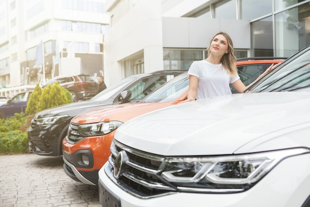Happy woman looking away dreamily, choosing new car to buy on car dealership parking area, copy space