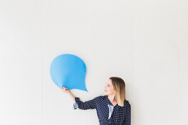Happy woman looking at blue speech bubble paper