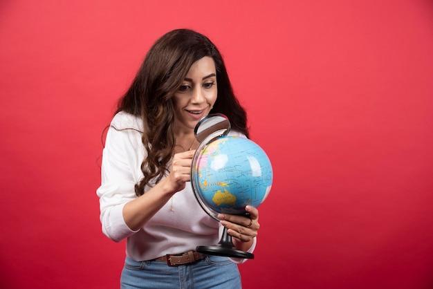 Donna felice che esamina globo con la lente d'ingrandimento. foto di alta qualità