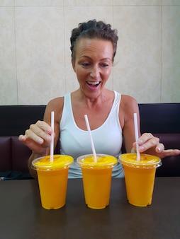 Happy woman looking at mango lassi drink inside indian restaurant vertical shot