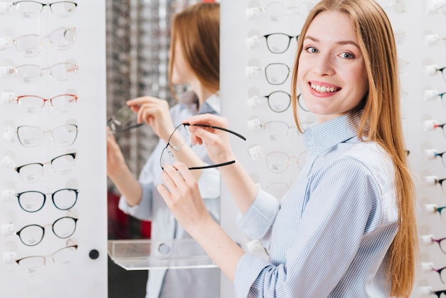 Happy woman looking for new glasses at optometrist