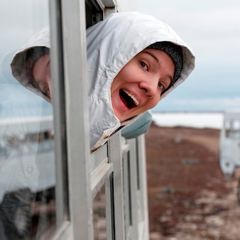 Happy woman looking out from the window of a bus, churchill, manitoba, canada