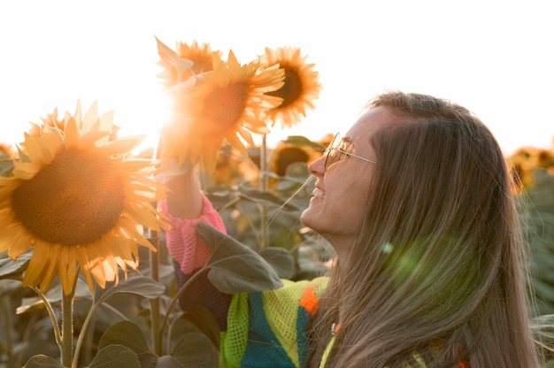 Happy woman looking at sunflower