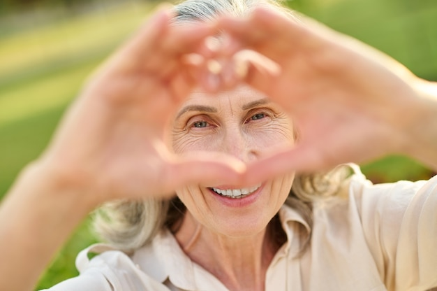 Happy woman looking through heart sign