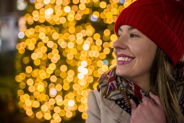Счастливый женщина, глядя вверх с рождественский свет в ночное время. счастливая девушка на улице, украшенная на рождество, глядя вверх