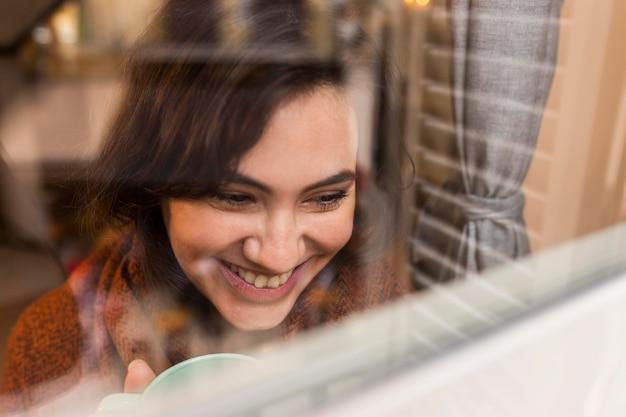 Donna felice che osserva sulla finestra