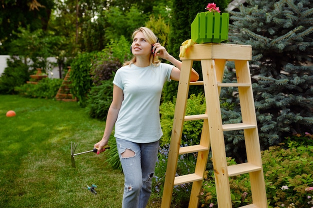 Happy woman looks on flower bed in the garden. female gardener takes care of plants outdoor, gardening hobby, florist lifestyle and leisure