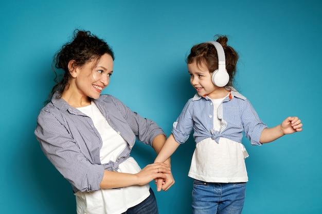행복 한 여자는 헤드폰에서 그녀의 작은 딸에 애정으로 보인다