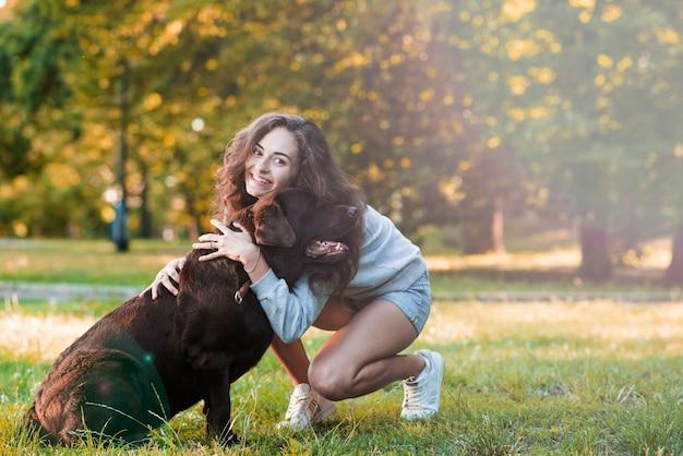 Happy woman loving her dog in garden