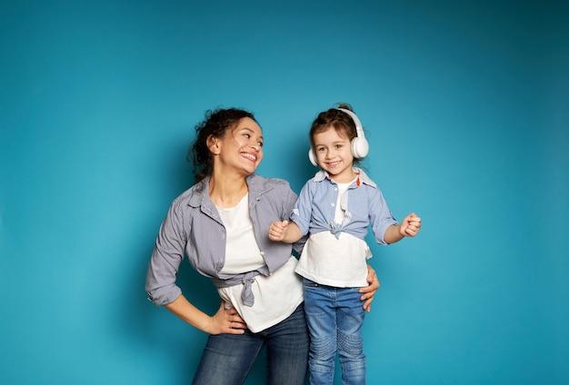 행복 한 여자는 헤드폰에서 그녀의 작은 딸을 사랑스럽게 본다