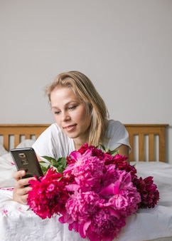 Happy woman lying on the bed wearing pajamas, enjoying tulip flowers bouquet of peony and using phone