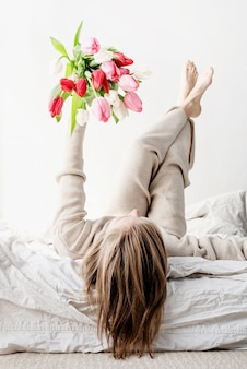 Happy woman lying on the bed wearing pajamas holding bright tulip flowers bouquet in outstretched hands