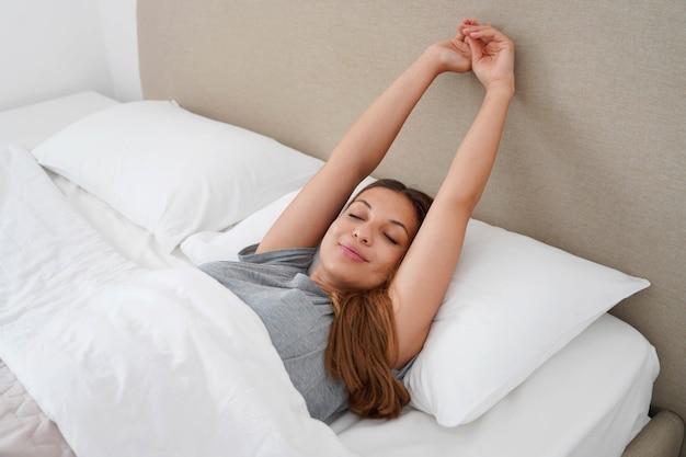 朝に腕を伸ばして目を覚ます快適なベッドに横たわって幸せな女性