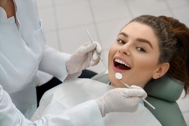 Счастливая женщина, лежа в кресле стоматолога, позирует.