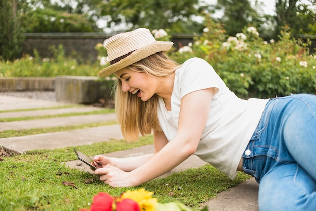 타블렛으로 잔디에 누워 행복 한 여자