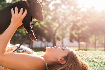 Happy woman lying on green grass holding dachshund at park