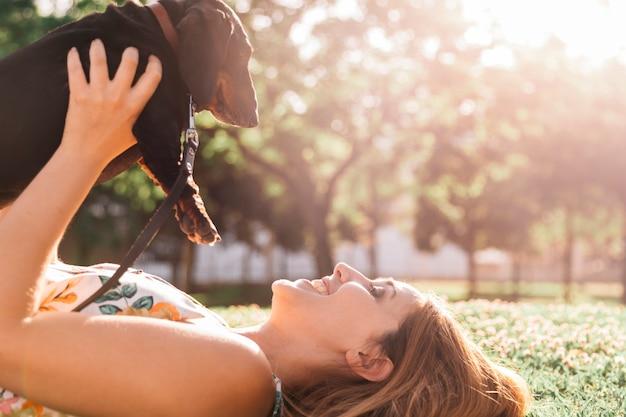 公園でdachshundを保持する緑の草に横たわっている幸せな女性