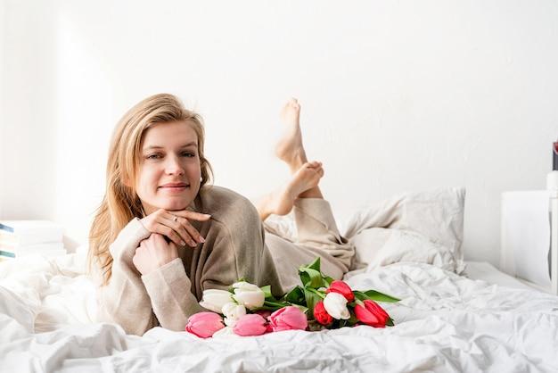 チューリップの花の花束とワインを楽しんで、パジャマを着てベッドに横たわって幸せな女性