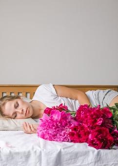 牡丹のチューリップの花の花束を楽しんで、パジャマを着てベッドに横たわって幸せな女性