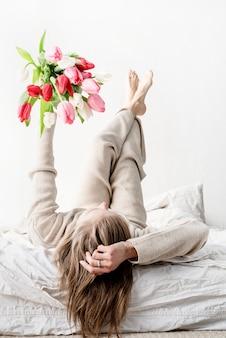 伸ばした手で明るいチューリップの花の花束を保持しているパジャマを着てベッドに横たわって幸せな女性