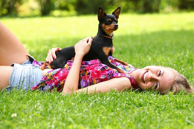 彼女の犬と草の上に横たわる幸せな女