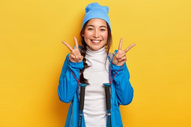 幸せな女性は平和のジェスチャーをし、トレッキングポールでポーズをとり、青い帽子とジャケットを着て、ハイキングを楽しんで、カメラを喜んで見て、黄色の壁に隔離されています