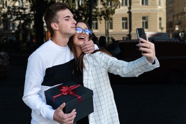 행복한 여자는 남자친구와 셀카를 만든다. 남자는 여자 친구에게 선물을 주고 그녀를 안아줍니다. 사랑에 웃는 커플.