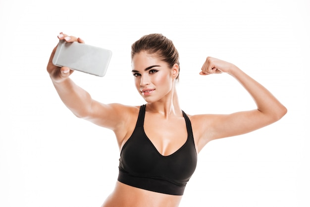 Happy woman making selfie photo on phone and showing biceps