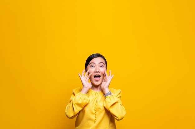 Счастливая женщина делая жест крика изолированный над желтой стеной