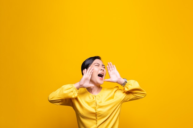 Happy woman making shout gesture isolated over yellow wall