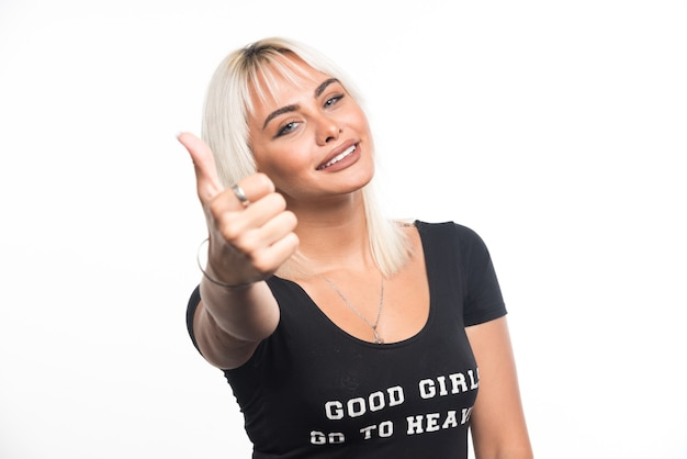 Happy woman making thumbs up sign on white wall.