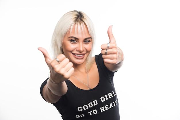 幸せな女性は白い壁に親指を立てるサインを作ります。