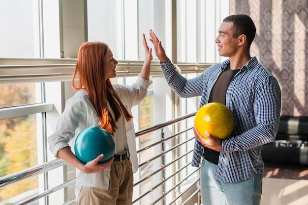 Happy woman and man holding colorful bowling balls medium shot