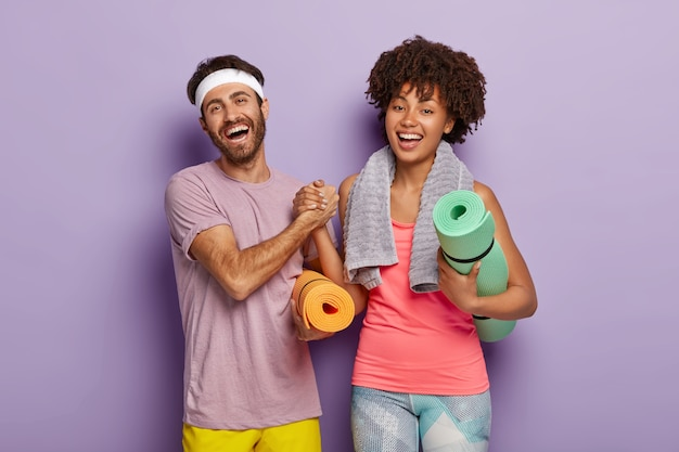 Happy woman and man keep hands together, dressed in sportwear, hold fitness mats
