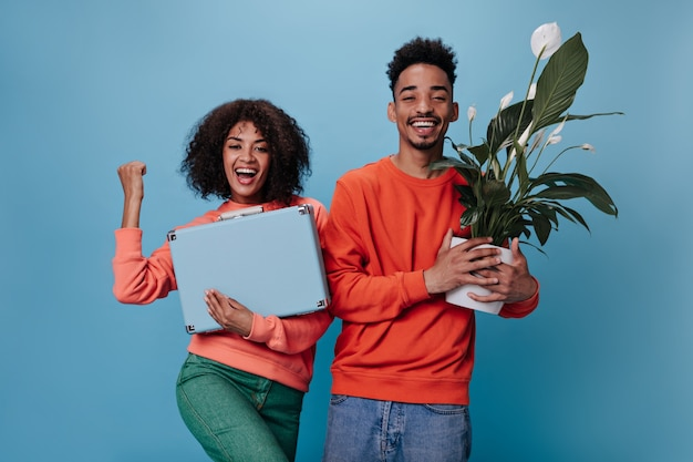 Happy woman and man in orange sweatshirts holding suitcase and plant
