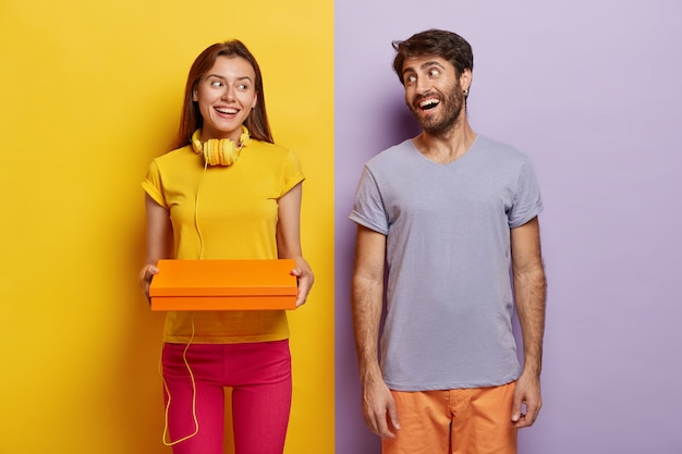 Happy woman and man satisfied after successful shopping day, hold small box, dressed in casual outfit, stand indoor against yellow and purple background.