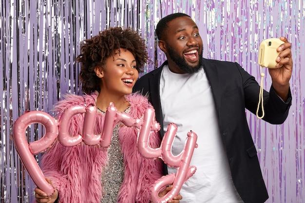 Felice donna e uomo con la pelle scura, espressioni felici, fa selfie sulla fotocamera, divertirsi alla festa di compleanno