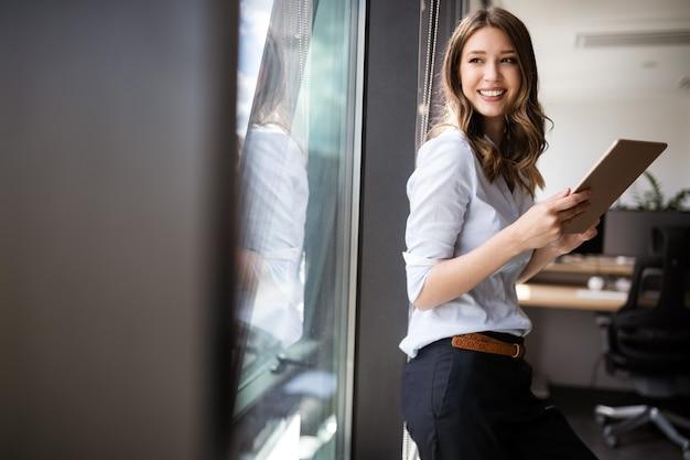 タッチパッドを持って何か良いことを考えている幸せな女性マネージャー