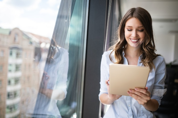 Happy woman manager holding touch pad and thinking about something good